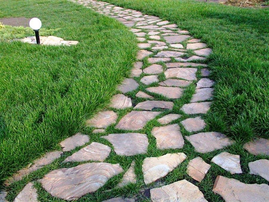 Тропинка из камней, уложенных на газон выглядит не менее эффектно