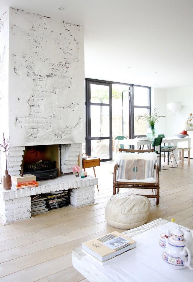 Классический дровяной камин прекрасно вписался в белоснежный интерьер скандинавского стиля