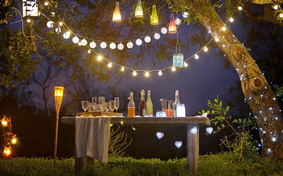 Подчеркнуть красоту сада можно подвесными гирляндами из светящихся шаров и фонариков
