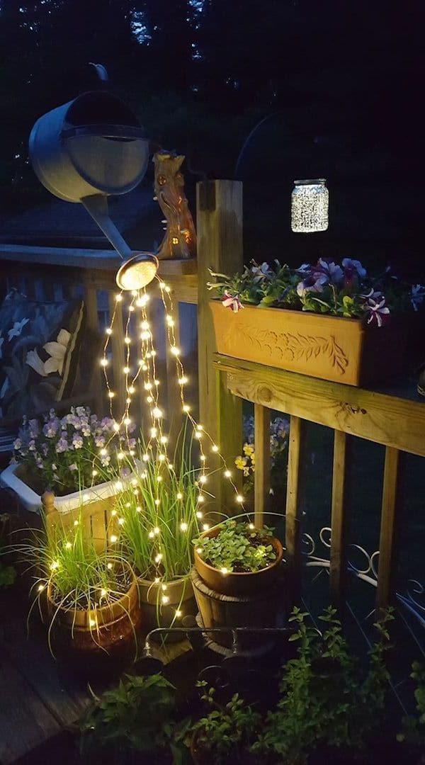 Непригодная лейка в хозяйстве будет служить в качестве подвесного светильника для цветочной клумбы
