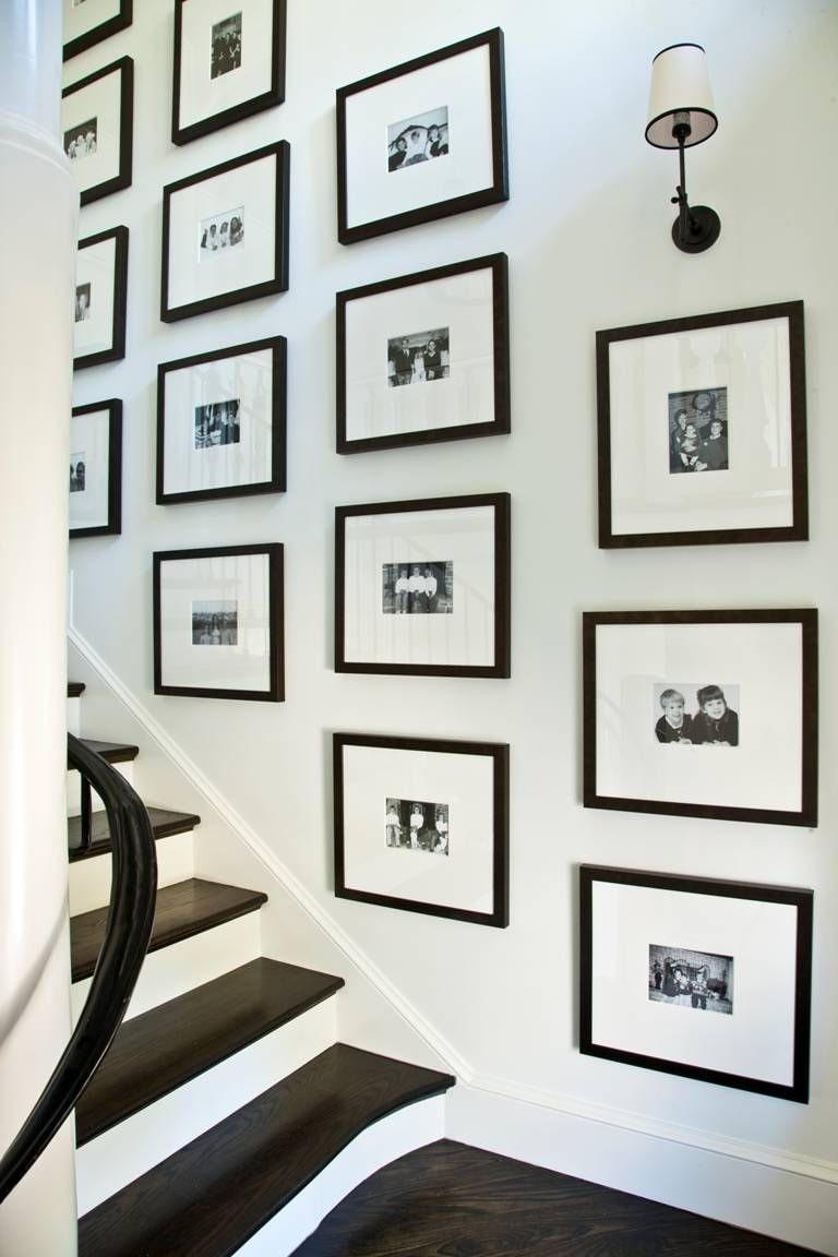 Семейные фото в одинаковых рамах на стене вдоль лестницы - отличное решение для декора частного дома