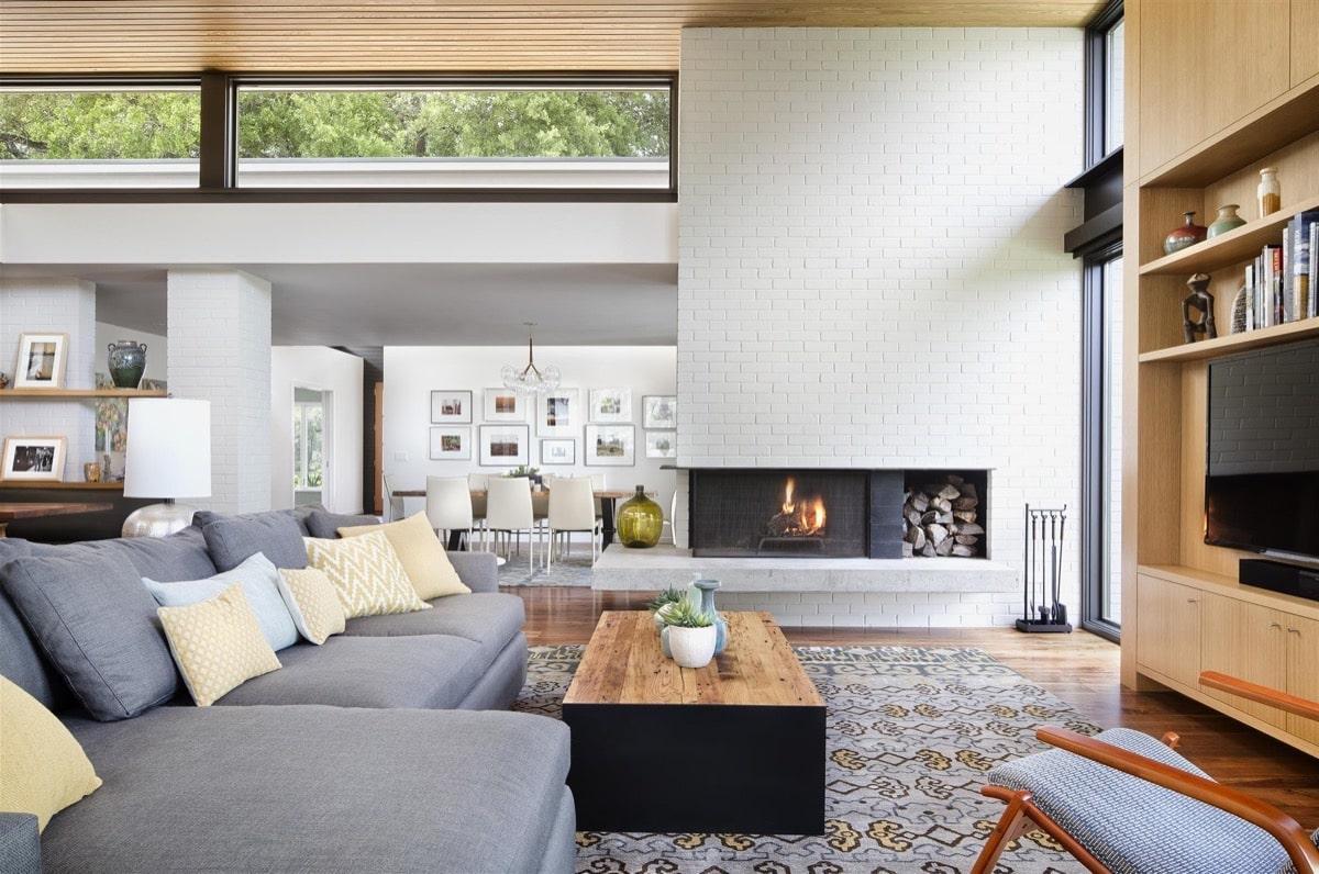 Красивый светлый дизайн интерьера гостиной частного дома с камином