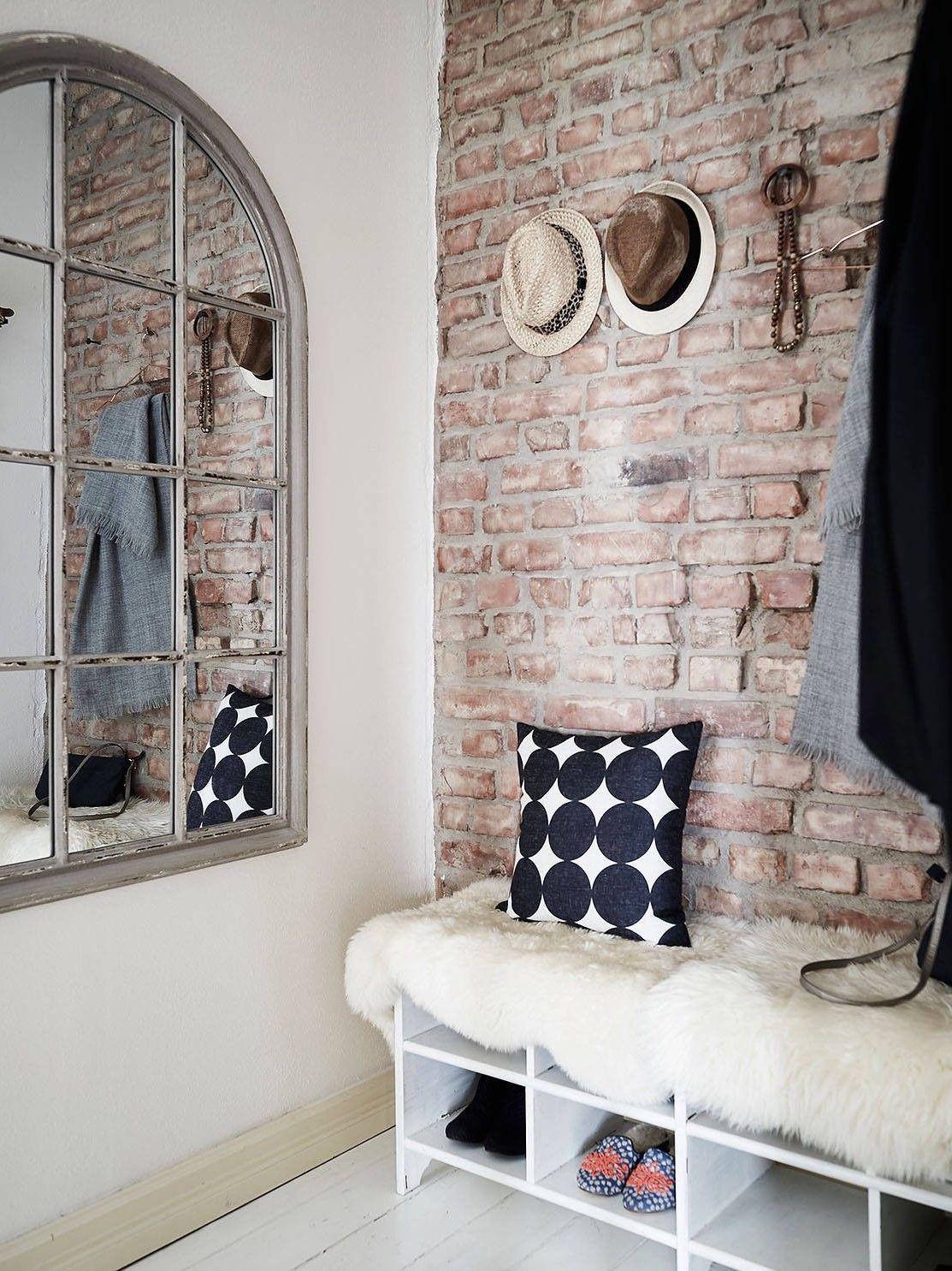 Дизайнерское зеркало соответствует кирпичной кладке на прихожей и выгодно акцентирует внимание