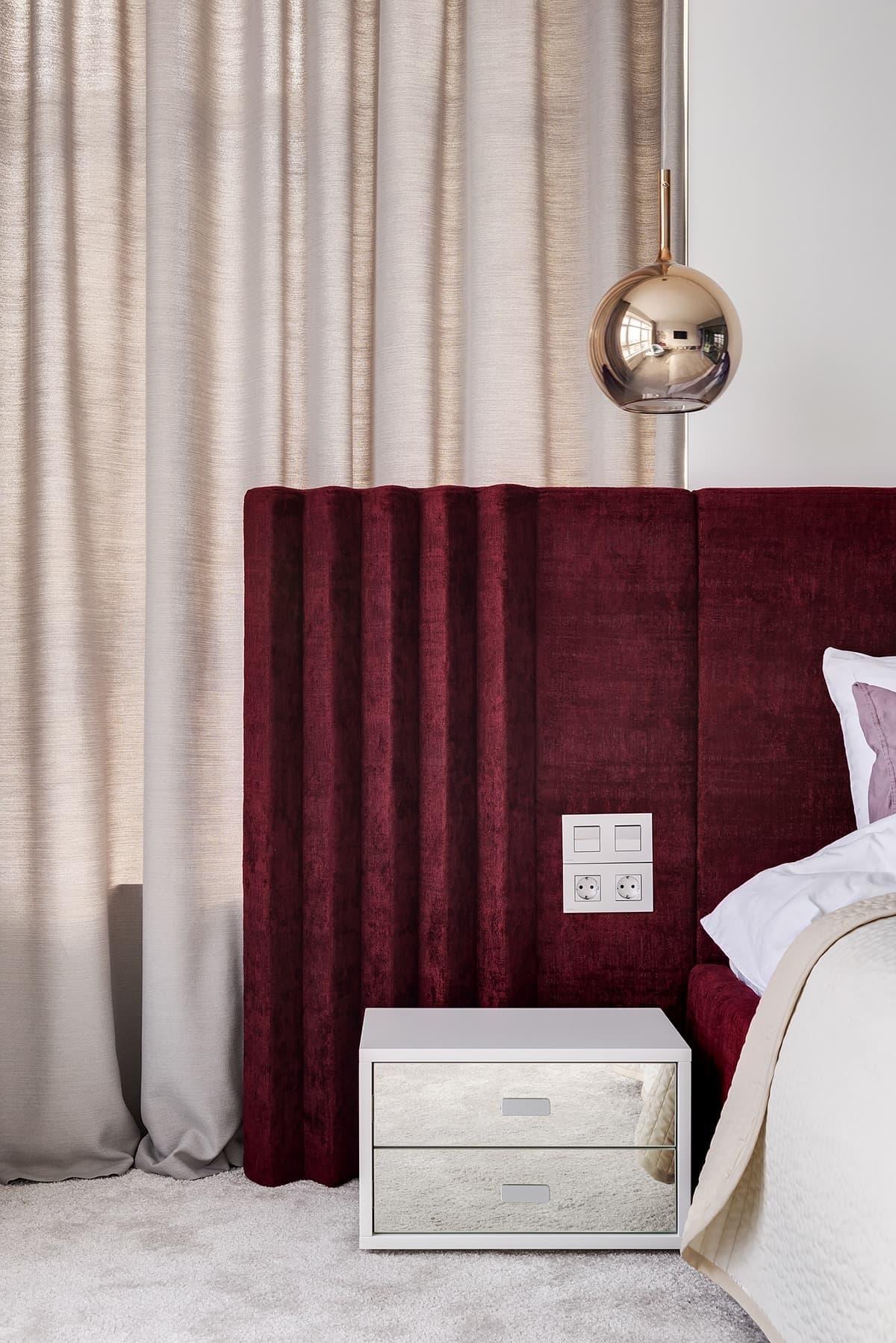 Бордовое изголовье кровати выступает как акцентный элемент на фоне бежевых штор в спальне