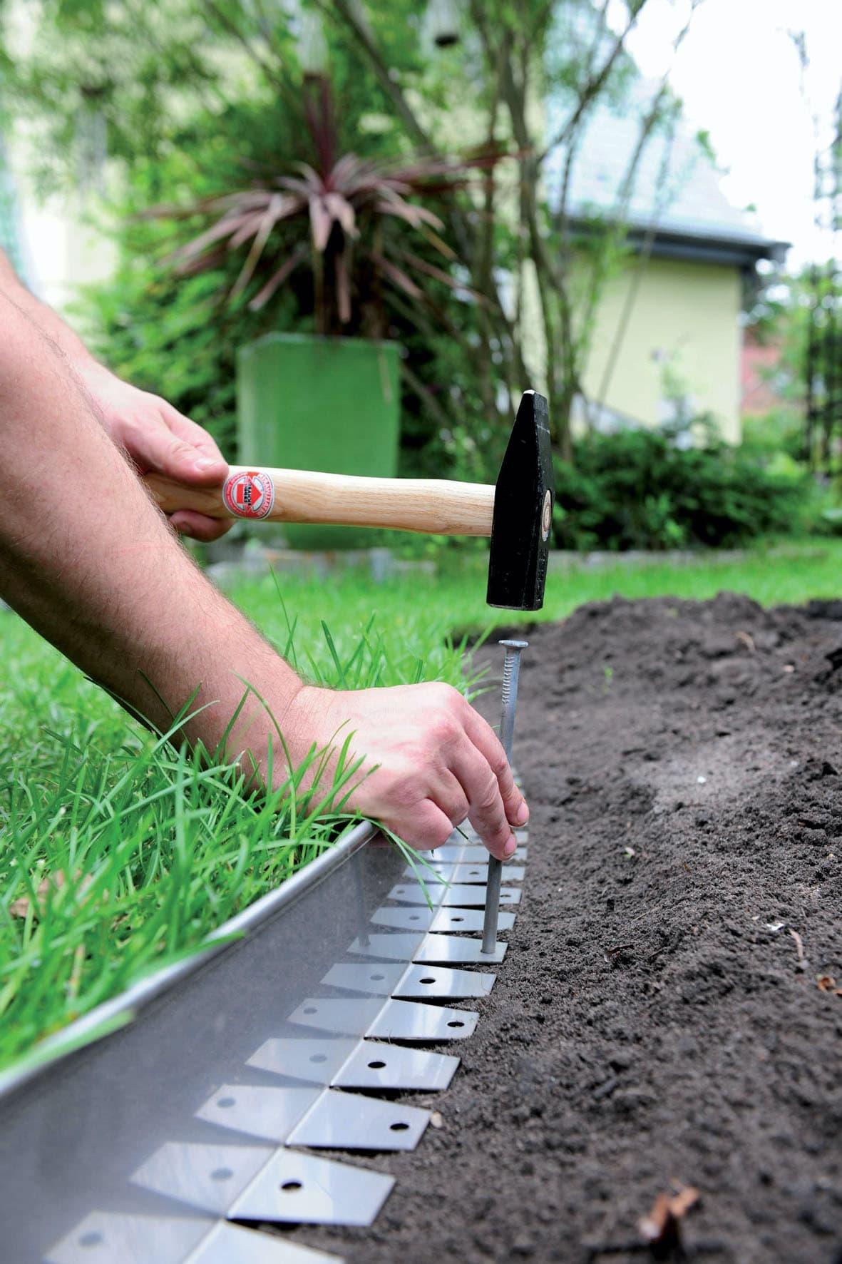 Установка бордюрной ленты не позволит повредить цветы на клумбе при покосе газонной травы