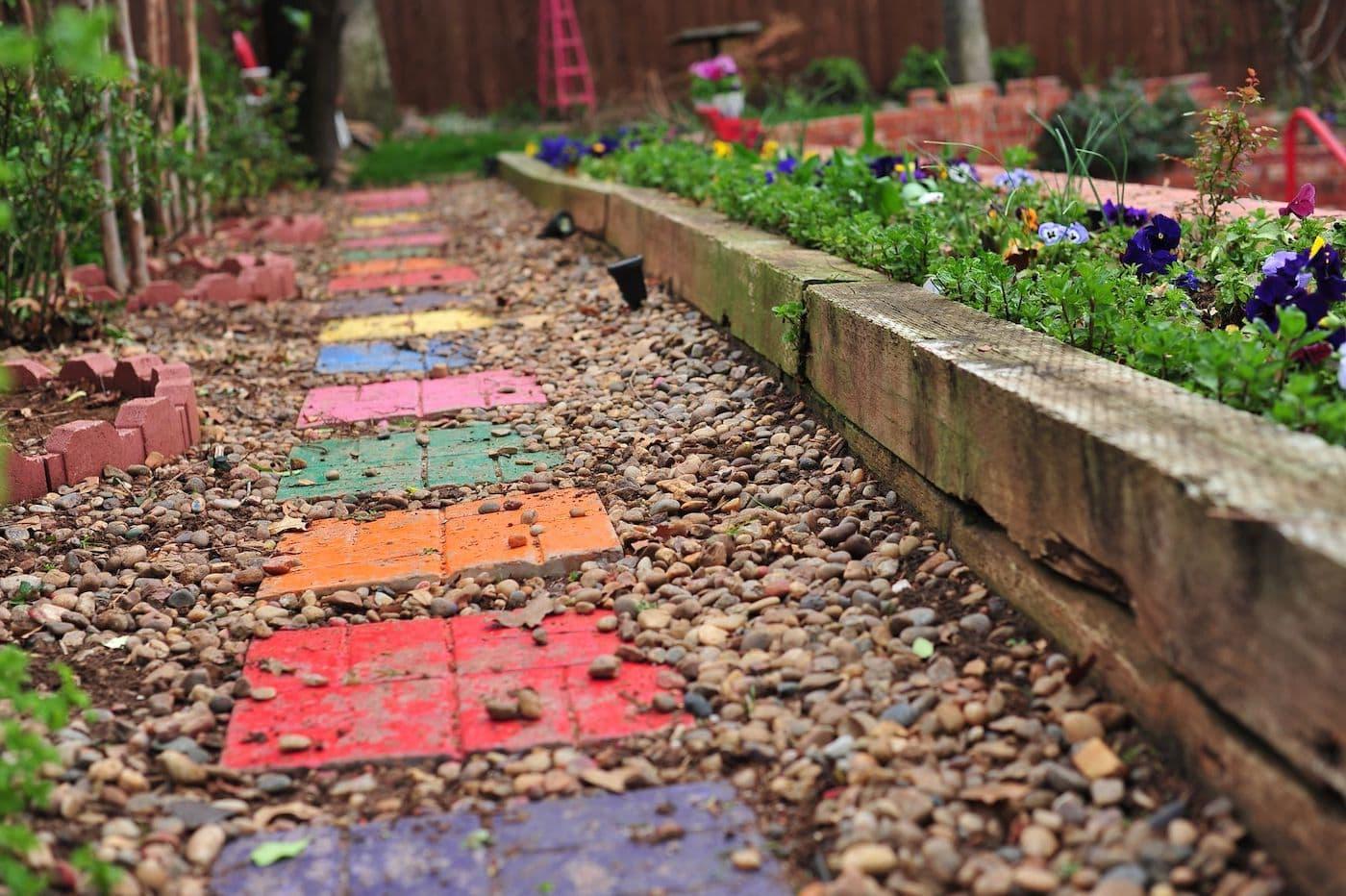 Разукрасив бетонную плитку и уложив ее на землю, можно получить оригинальную садовую дорожку